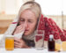 Sick blond girl has caught a cold. She is lying in bed and touching tissue to her nose. The lady closed her eyes with desperation. There are pills and vitamins on the table